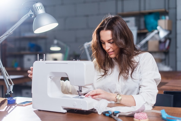 Attractive caucasian seamstress working stitching with sewing machine at her workplace in studio loft interior
