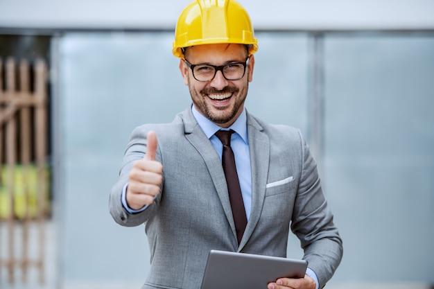 Архитектор привлекательного кавказца усмехаясь элегантный в костюме, с eyeglasses и шлемом на голове держа таблетку пока стоящ на строительной площадке и дающ большие пальцы руки вверх.