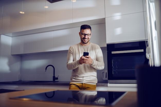 魅力的な白人の笑みを浮かべて男はカジュアルな服を着てキッチンカウンターにもたれて、スマートフォンを使用してメッセージを送信します。ホームインテリア。