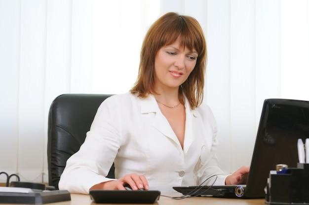 Привлекательная кавказская белая коммерсантка брюнет работая на компьтер-книжке в ее рабочей станции держа компьютерную мышь.