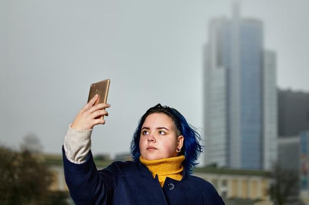 青い髪の魅力的な白人の白人の女の子は、スマートフォンの助けを借りて自分の写真を撮っています。