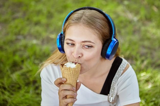 긴 금발 머리와 이어폰 약 25 세 매력적인 백인 백인 젊은 여자는 공공 공원에서 산책하는 동안 아이스크림을 먹고 있습니다.