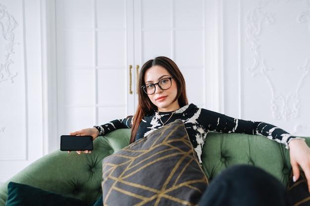 Привлекательная кавказская женщина в наушниках, расслабляясь на удобном диване у себя дома и слушая музыку.