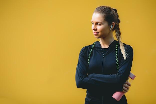 赤黄色の孤立した背景にトレーニングの後のワイヤレスヘッドフォン飲料水とスポーツスーツの魅力的な白人女性