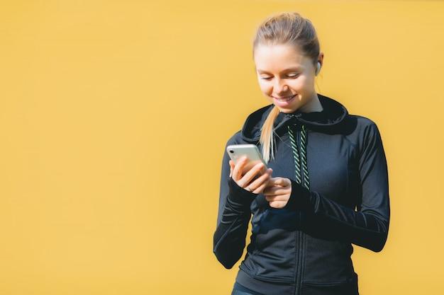 オレンジで音楽を聴く彼女の電話を使用してワイヤレスヘッドフォンでスポーツスーツの魅力的な白人女性