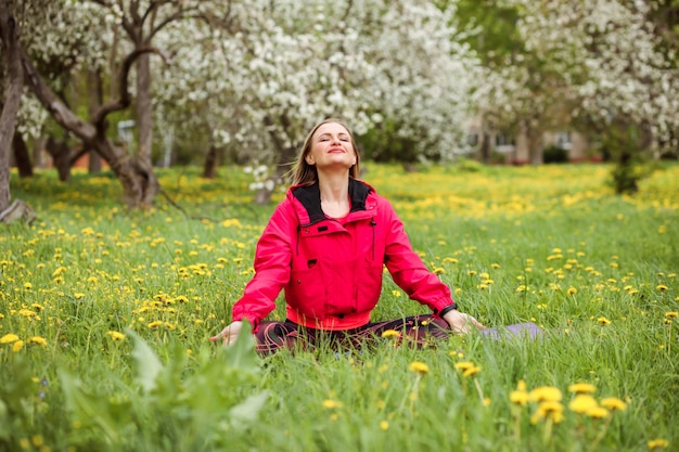 Attractive caucasian woman meditates outdoors in the blooming garden