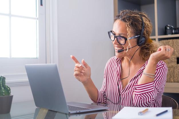 魅力的な白人女性がヘッドセットを身に着けてホームオフィスの部屋に座って、ラップトップを使用した教育ウェビナーに参加します。クライアントとのビデオ通話イベントまたはリモートで友人との個人的なチャットの概念