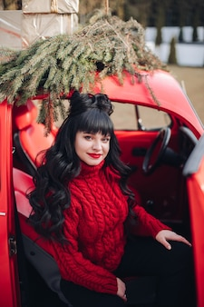 Attraente donna caucasica si siede al posto di guida dell'auto e sorride