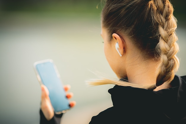 公園で走っている間彼女の電話、ワイヤレスヘッドフォンを使用して魅力的な白人女性