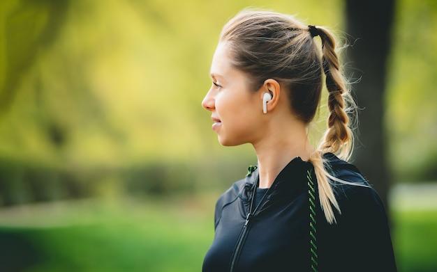 Привлекательная кавказская женщина используя ее телефон, беспроволочные наушники пока бегущ в парке