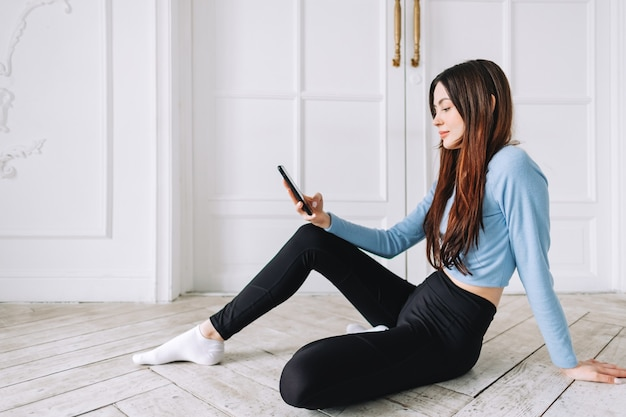 Привлекательная кавказская женщина с помощью мобильного телефона после фитнеса дома.