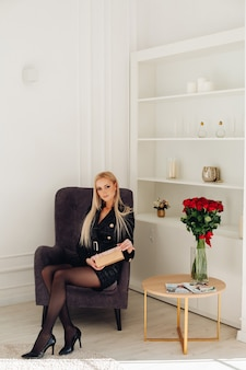 Attractive caucasian woman with blonde hair in stylish black dress in luxurious apartment