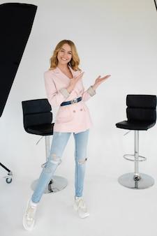 Привлекательная кавказская женщина со светлыми волнистыми волосами в белой рубашке, синих брюках держит руки на талии и улыбается в студии
