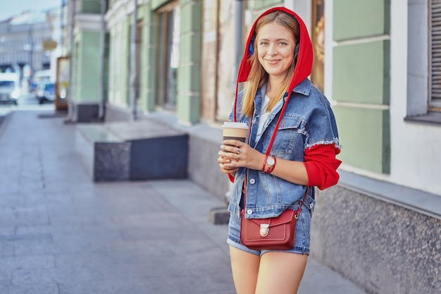 Attractive caucasian young cheerful woman about 25 years old in red hoodie and with long blond hair is drinking coffee from paper cup.