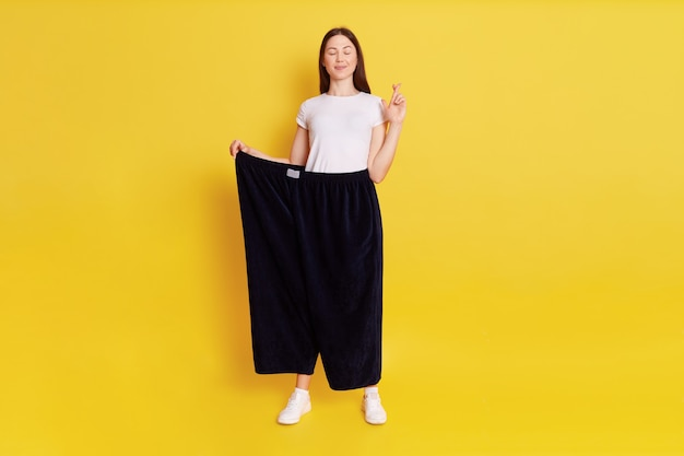 Attractive caucasian young female wearing old huge pair of pants, weight loss, stands with close eyes, keeps fingers crossed, make wish to not get fat again, isolated over yellow wall.