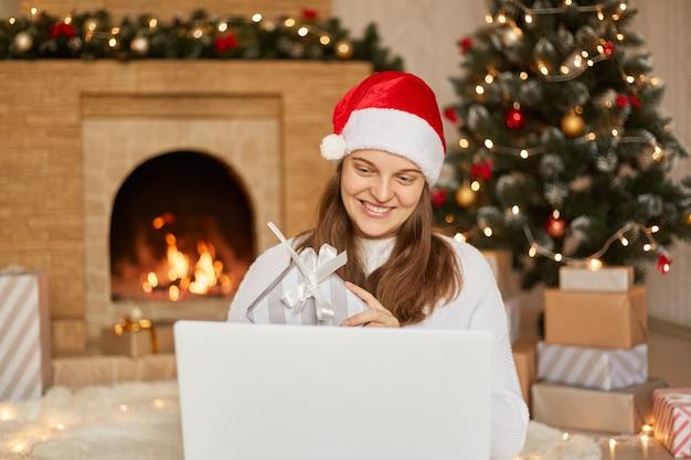 クリスマスツリーと暖炉の近くの自宅の床に座っている間、彼女のラップトップでビデオ通話をしているサンタ帽子の魅力的な白人の若い笑顔の女の子。カメラにギフトボックスを見せて、笑顔。