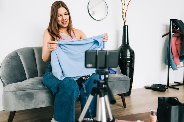 소셜 미디어에서 그녀의 블로그를 통해 새 옷을 보여주는 매력적인 백인 젊은 여자 비디오 블로거