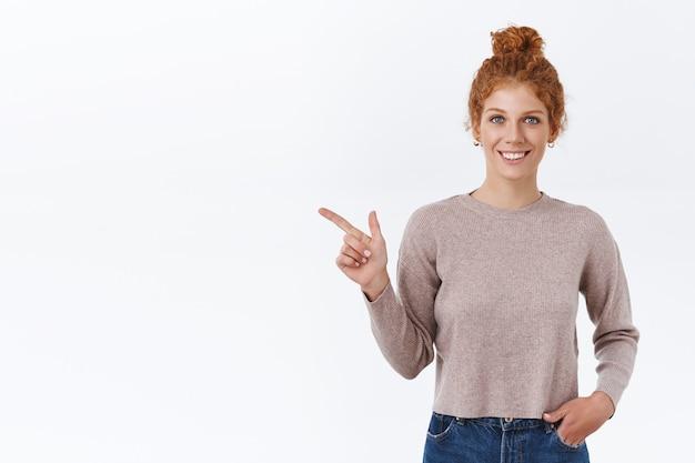 乱雑なパンでとかされた巻き毛の魅力的なカリスマ的な赤毛の女性、ポケットに手を握り、左を指して、製品を紹介し、プレゼントを宣伝するように満足して笑って、白い壁に立っている