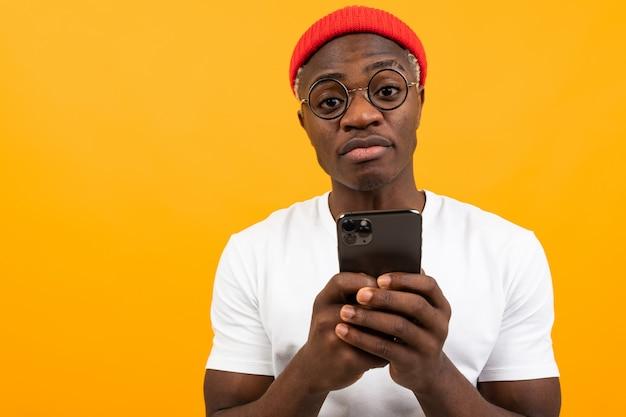 コピースペース付きの黄色のスタジオで彼の手にスマートフォンを持っている白いtシャツの魅力的な魅力的な黒人男性