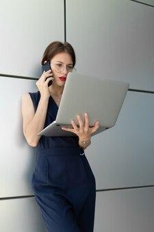 그녀의 손에 노트북과 매력적인 매력적인 비즈니스 여자는 건물의 사무실 센터의 벽에 기댄 전화