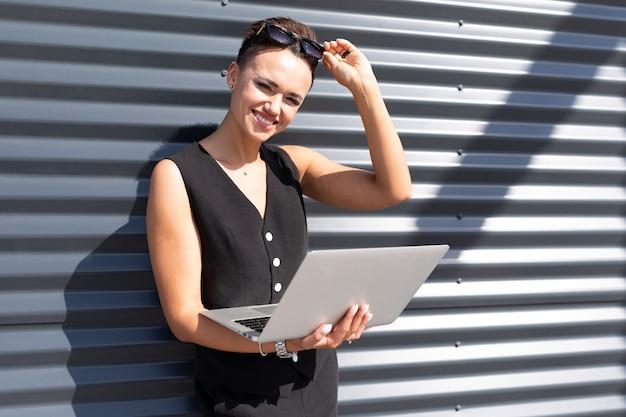 ビジネスセンターの建物の壁に立つ彼女の手にラップトップを持つ魅力的な魅力的なビジネス女性