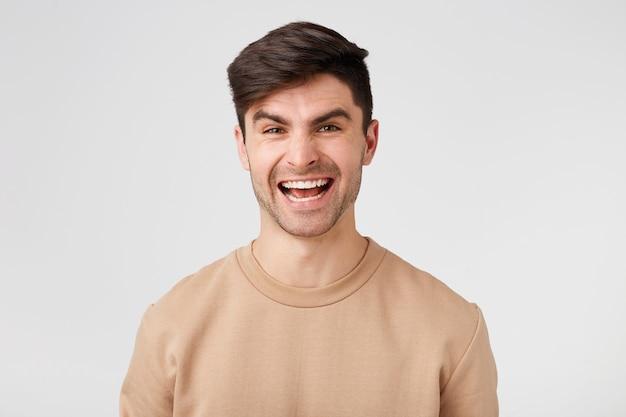 Привлекательная очаровательная жизнерадостная улыбающаяся брюнетка в обнаженном свитере изолирована на белой стене