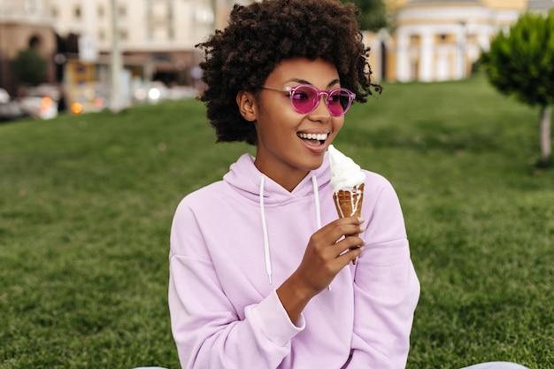 분홍색 선글라스를 쓴 매력적인 행복한 여성, 세련된 대형 후드티 미소를 짓고 야외에서 아이스크림을 먹습니다
