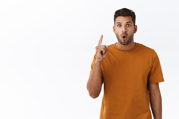 Attractive charming hipster male coworker suggest his solution method, raise index finger in eureka, lightbulb gesture, folding lips saying his plan, introduce own concept during office meeting