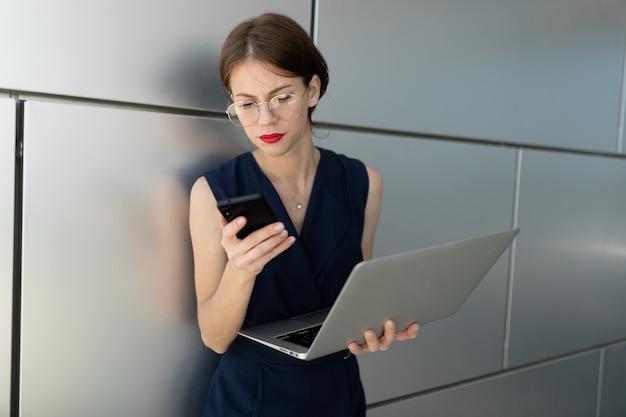 그녀의 손에 노트북과 붉은 입술을 가진 매력적인 매력적인 젊은 비즈니스 여자는 건물의 사무실 센터의 벽에 기댄 전화로 약속을합니다