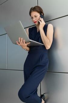 그녀의 손에 노트북과 붉은 입술을 가진 매력적인 매력적인 젊은 비즈니스 여자는 건물의 사무실 센터의 벽에 기댄 전화