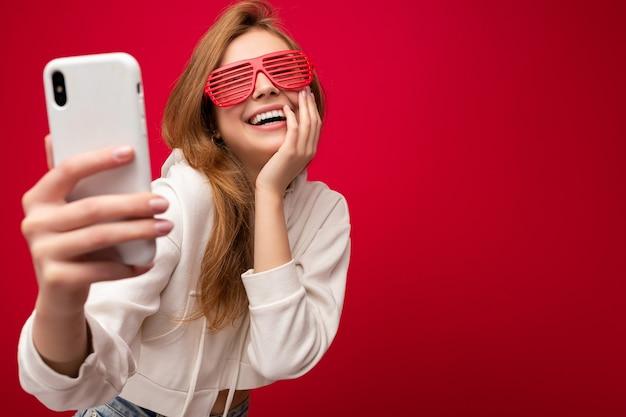매력적인 매력적인 젊은 웃는 행복 한 여자 잡고 벽 배경 위에 고립 된 세련 된 옷을 입고 셀카를 복용하는 휴대 전화를 사용 하여.