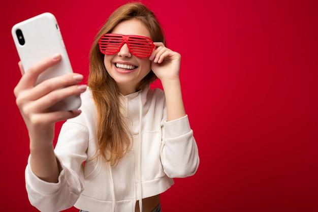 Привлекательная очаровательная молодая улыбающаяся счастливая женщина, держащая и использующая мобильный телефон, носящая селфи