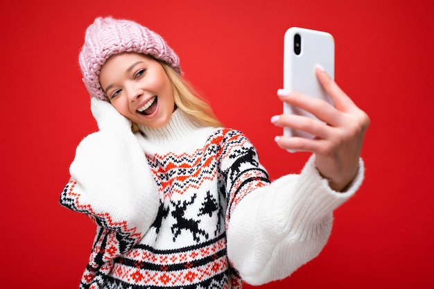 Attractive charming young smiling happy woman holding and using mobile phone taking selfie wearing