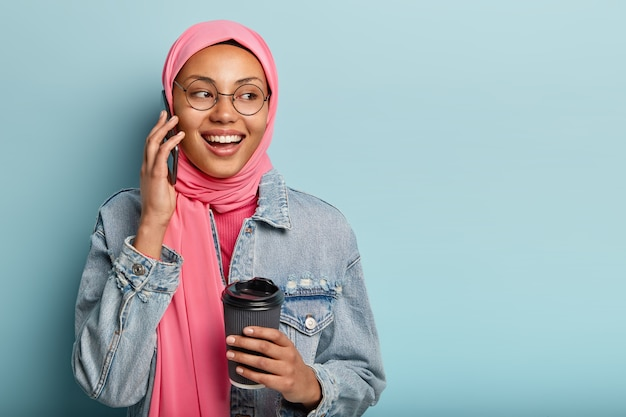 Attractive cheerful arabian woman has telephone conversation with close friend, holds disposable cup of coffee, looks away