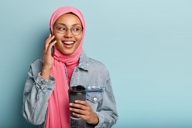 매력적인 쾌활한 아라비아 여성은 가까운 친구와 전화 통화를하고 일회용 커피 한잔을 들고 멀리 보입니다.