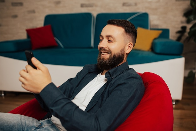 Attractive cheerful bearded guy sitting on armchair and are using cell playing game having fun.
