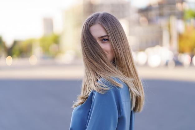 Привлекательная веселая блондинка с развевающимися длинными волосами, улыбаясь смеясь в городе