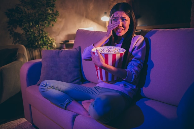 Привлекательная веселая брюнетка молодая женщина, сидящая на диване