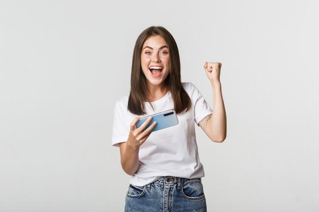 Привлекательная веселая брюнетка девушка выигрывает в мобильной игре, держит смартфон и радуется.