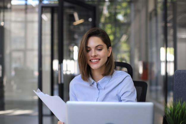 Привлекательная жизнерадостная бизнес-леди, проверка бумажных документов в офисе, работая на ноутбуке.