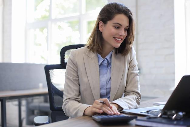 Привлекательная жизнерадостная бизнес-леди, работающая на ноутбуке в современном офисе.