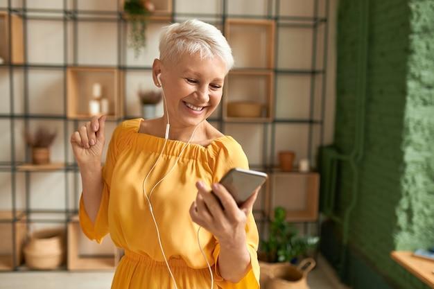 携帯電話を使用して、イヤホンで音楽を聴いて、踊って、幸せな楽しい表情を持っている黄色のドレスを着た魅力的な陽気な女性年金受給者