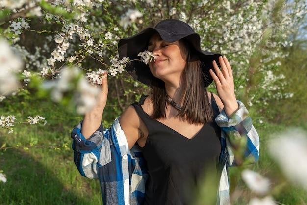 カジュアルなスタイルで、春に咲く木々の間で帽子をかぶった魅力的な陽気な女の子