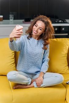 魅力的な陽気な女の子は、モダンなスタイリッシュなキッチンでselfie写真になります。居心地の良い家で黄色のソファで楽しんでいる若い女性。