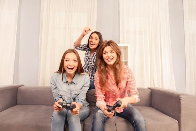 楽しんでビデオゲームをプレイする魅力的な陽気な女の子