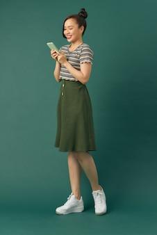 매력적인 쾌활한 여성 인플루언서는 녹색 배경에 어깨에 배낭을 메고 전화를 들고 있습니다.