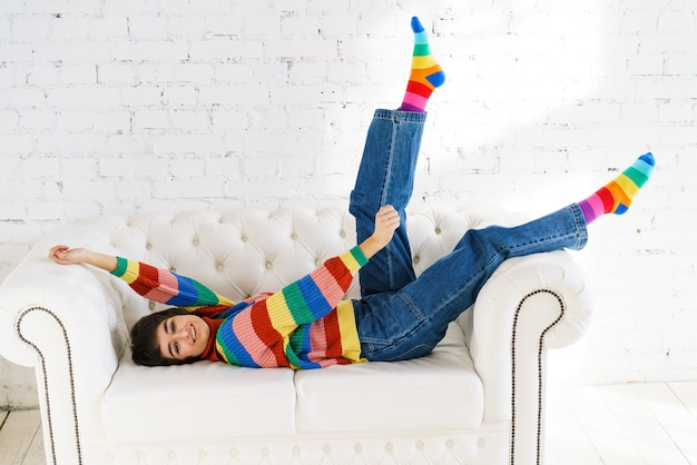 魅力的な陽気な女性は、ストライプの短いセーターを着て承認を表明するために手を上げます...