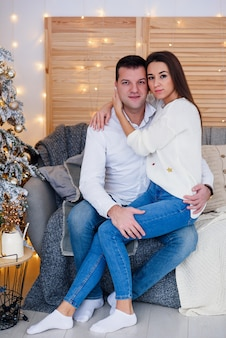 Attractive cheerful man and woman sitting near christmas tree and hugging each other. new year's eve.