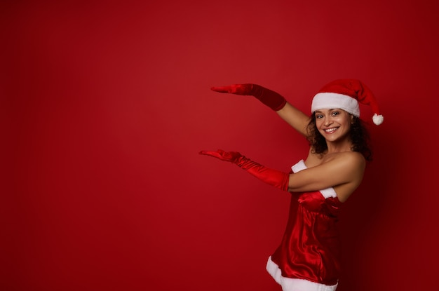 산타 카니발 의상을 입은 매력적인 혼혈 여성은 빨간색 배경에 광고를 위한 복사 공간을 보유하고 있으며 카메라를 바라보는 아름다운 이빨 미소로 미소를 짓고 있습니다. 크리스마스와 새해 개념