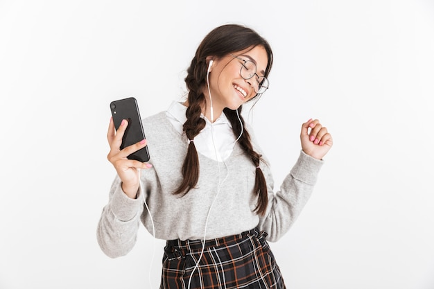白い壁の上に孤立して立っている、イヤホンで音楽を聴く、携帯電話を持って、踊るからユニフロを身に着けている魅力的な陽気な女子高生